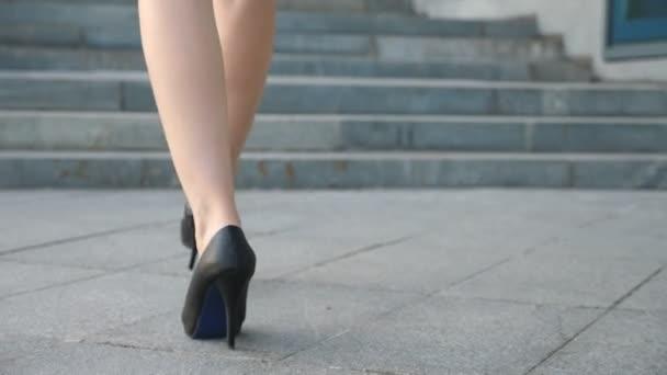 Ženské nohy v botách na podpatku chůze na schodech. Nohy podnikatelka posílení na schodiště. Elegantní žena, lezení na schodiště. Mladá dívka šlápnutí na městské ulici. Detailní záběr Zpomalený pohyb