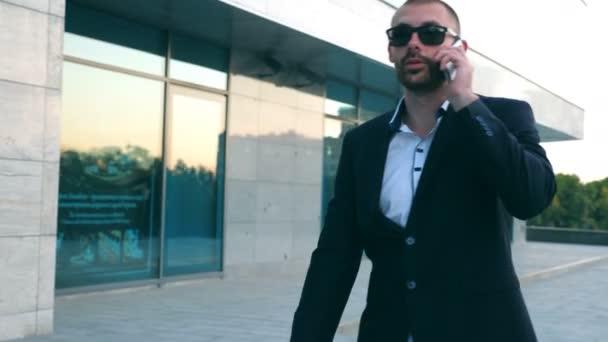 Podnikatel v sluneční brýle pěší ulici a mluví o telefonu. Mladí obchodní muž mluvit na mobil během dojíždění do práce. Hezký chlap v obleku bavit venkovní. Zpomalený pohyb