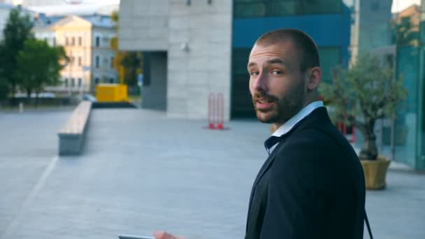 Pohledný podnikatel mluví o telefonu poblíž kanceláře a při pohledu na fotoaparát. Mladí obchodní muž mluví na mobil outdoor moderní budovy. Portrét člověka bavit venku. Detailní záběr