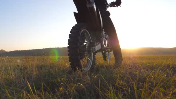 Unrecognizable motorcycle rider sits on his motorcycle amid large field on beautiful sunset background. Sportsman admires landscape while sitting on motorcycle. Slow motion Close up