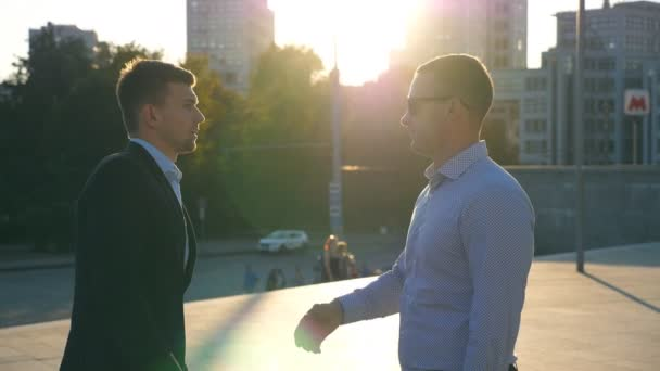 Two young business men standing outdoor at city square and talking. Businessmen meet and speaking outside with cityscape at background. Communication of happy colleagues. Close up Slow motion