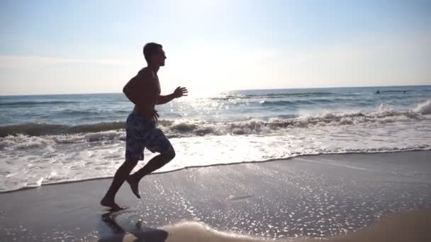 Young sporty man running on the sea beach at morning. Athletic guy jogging along coast on a sunny day. Male sportsman exercising outdoor. Healthy active lifestyle. Side view Slow motion