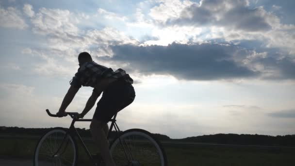 Silueta mladík na koni na vintage kolo s krásného západu slunce na obloze v pozadí. Chlap na kole v zemi silnici. Mužské cyklistu jedoucího pevné ozubené kolo. Zdravý aktivní životní styl zpomalené