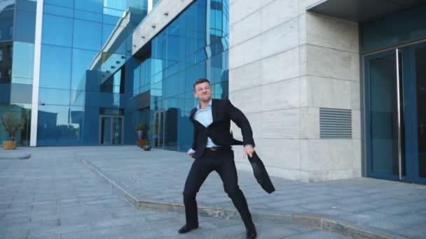 Boldog fiatal üzletember ruha örül a jó üzlet a város utca. Sikeres irodai dolgozó, a táska segítségével csinál győzelem dance, modern épület közelében. Jóképű férfi élvezi eléréséhez. Lassú mozgás