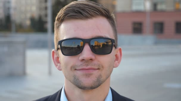 Portrait of happy businessman in sunglasses with cityscape at background. Handsome business man looking at the camera and smiling. Face of cheerful guy. Blurred background. Slow motion Close up