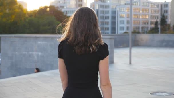 Nelze rozpoznat dívka v černých šatech, chůzi po městské ulici. Atraktivní podnikatelka děje ve městě. Dívka, krokování venkovní. Zadní pohled zezadu zpomalené Detailní záběr