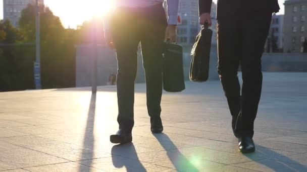 Feet of two businessmen with briefcases walking in city street at sunset time. Partners commute to work together. Confident guys being on his way to office. Colleagues going outdoor. Slow motion