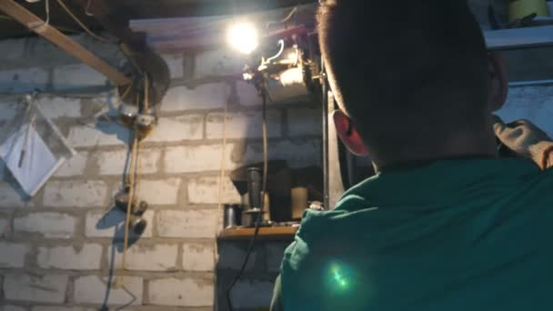 Mužské mechanik opravuje auto detaily. Muž v pracovní oděvy pracuje v garáži nebo dílně. Tvrdá práce koncept. Zadní pohled zpomalené Detailní záběr