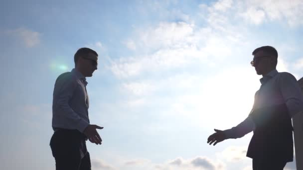 Two successful businessmen meeting in city and greet each other. Young male colleagues shaking hands outdoor. Handshake of business partners outdoor. Blue sky at background. Slow motion Low angle view