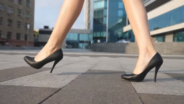Feet of young businesswoman in footwear on high-heeled going in urban street. Slim female legs in black shoes on high heels walking at city square. Elegant girl stepping to work. Slow motion Close up