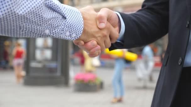 Dvě mladé mužské kolegy potřásl rukou s pozadí rozmazané města. Důvěru podnikatele navzájem pozdrav v městském prostředí. Handshake obchodních partnerů venkovní. Zpomalené Detailní záběr