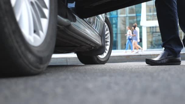 Businessman opens and holds door of car for beautiful young woman. Slim legs of businesswoman in shoes on high heels getting out of auto. Close up Slow motion Low angle view