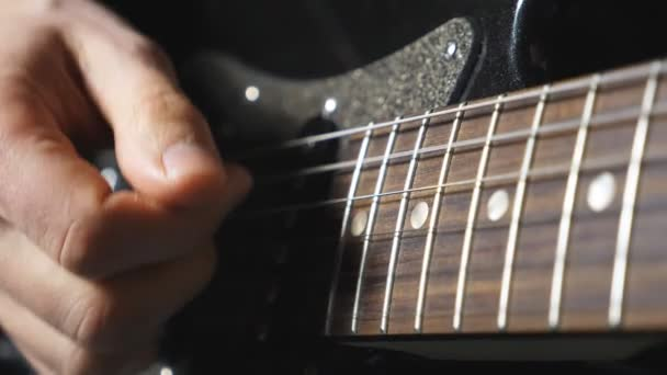 Close up fingers of guitarist strumming the strings. Hand of male musician playing on electric guitar. Arm of adult man plays on a musical instrument. Guy composing a new melody. Slow motion