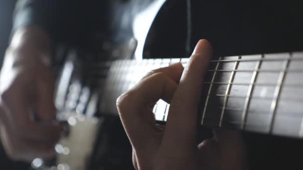 Férfi zenész játszik a gitár címere. Közelről ujjak gitáros penget az húrok. Kezében a srác végző egyéni a rock zene. Felnőtt ember játszik valamilyen hangszeren. Lassú mozgás