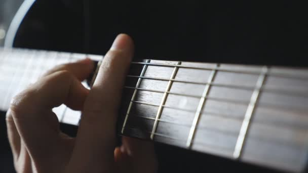 Close up male fingers of guitarist strumming the strings. Hand of guy performing solo of rock music. Arm of musician playing on electric guitar. Adult man composing a new melody. Slow motion