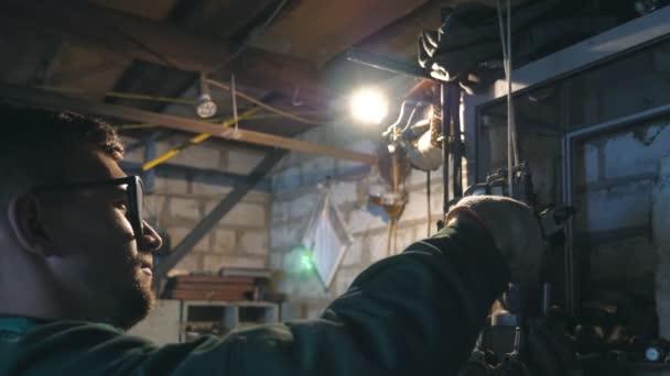 Mechanik dělá svou práci pomocí nástroje. Muž v pracovní oděvy pracuje v garáži nebo dílně. Profil mladých mužů servisního pracovníka v brýlích. Tvrdá práce koncept. Dolly zastřelených zpomalené Detailní záběr