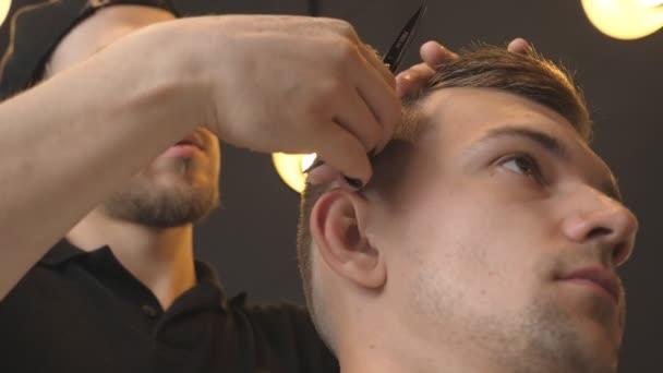Mužské holič česání a stříhá vlasy mladých zákazníků kartáč a nůžek v salonu. Kavkazská kadeřník stříhání vlasů svého klienta v holičství. Proces, kadeřnictví. Detailní záběr Zpomalený pohyb