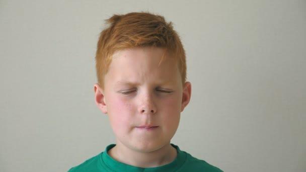 Portrét chlapce vážný zrzavé vlasy s pihy. Rozkošné hezký dítě při pohledu do kamery vnitřní. Zblízka emoce mužského potomka se smutným výrazem na tváři. Zpomalený pohyb