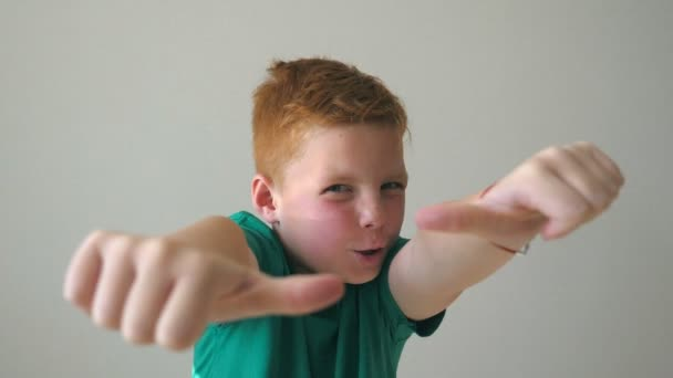 Adorable baby rejoicing achievement and showing thumbs up. Close up emotions of male child with joy expression on face. Portrait of handsome happy red hair boy with freckles indoor. Slow motion