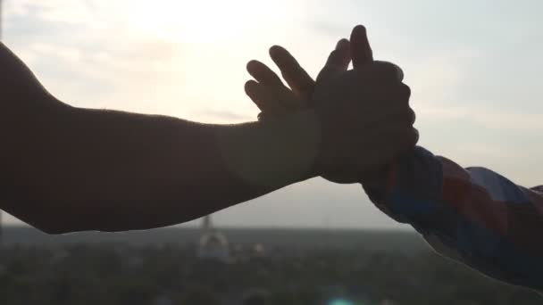 Friendly handshake of two unrecognizable men on cityscape background. Close up of men greeting with handshake. Two good friends having firm handshake outdoor. Friendship concept. Slow motion