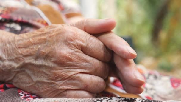 Venku jsou vrásčité paže starší ženy. Babička si hladí ruce venku. Zavřít boční pohled Zpomalený pohyb