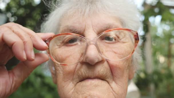 alte Frau richtet ihre Brille auf und blickt in die Kamera. Porträt der Großmutter im Freien. Zeitlupe in Nahaufnahme