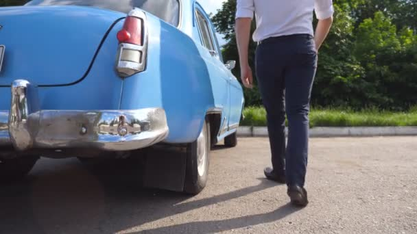 Man opens and holds the door of old car for the beautiful young woman in high heels shoes. Guy opening door of vintage automobile for female passenger. Girl getting out of retro auto. Slow Motion