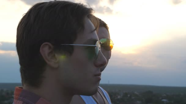 Profile of handsome gay boys in sunglasses standing on the edge of rooftop and talking. Young male couple relaxing on roof of high-rise building and enjoying beautiful cityscape. Close up Slow motion