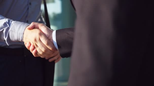 Close up of successful businessmen greeting each other near office building. Two young colleagues meeting and shaking hands in urban environment. Handshake of business partners outdoor. Slow motion