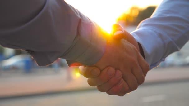 Dva úspěšní podnikatelé se zdravili na pozadí parkoviště. Mladí kolegové se setkávají a potřásají si při západu slunce rukou. Podání ruky venku. Zpomalený pohyb