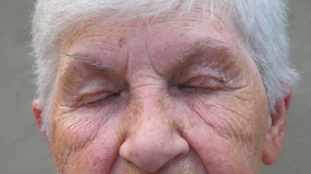 Nahaufnahme der grauen Augen der Großmutter mit Falten um sie herum. Porträt einer Seniorin, die mit einem traurigen Anblick in die Ferne blickt. Trauer Gesichtsausdruck einer älteren Frau