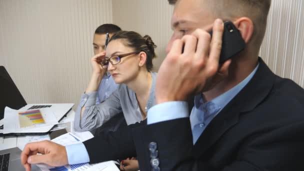 Skupina mladých obchodních lidí, kteří sedí u stolu v moderní kanceláři a pracují na novém projektu. Kolegové si během pracovního procesu pozorně Prohlédněte obrazovku přenosného počítače. Pracovníci systému Office zaneprázdnění podnikání