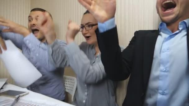 Mladí obchodní lidé oslavují úspěch zházejí dokumenty a vykazují radostné emoce. Pracovníci sady Office se po tvrdé práci radní s úspěchem. Tvůrčí tým pracující v moderní kanceláři. Zpomaleně