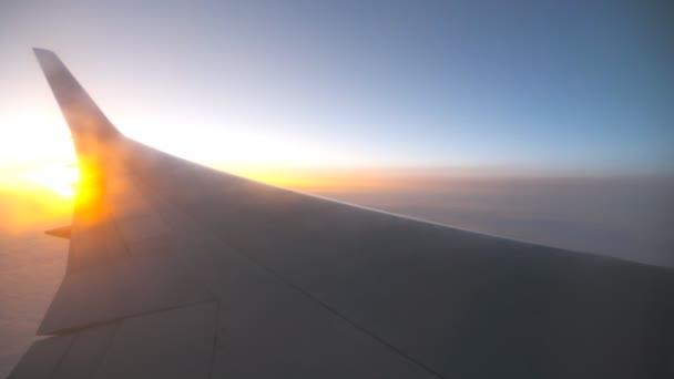 Blick vom Flugzeugfenster auf Sonnenaufgang oder Sonnenuntergang. Tragfläche eines Flugzeugs, das mit Sonnenlicht über den Wolken fliegt. Flugzeugflug am Himmel. Konzept des Reisens per Flugzeug. Reise mit dem Flugzeug mit schönem Hintergrund