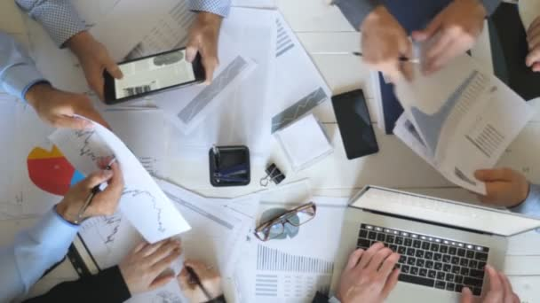 Vista superiore alle mani di imprenditori di lavorare in modo efficiente con i documenti. Gruppo di lavoratori che si siede al tavolo in ufficio. Team creativo occupato dello sviluppo del business. Vista di lavoro disordine sulla scrivania in ufficio. Mo lento