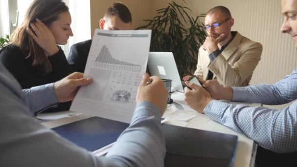 Group of young businessmen sitting at table in modern office and working on new project. Colleagues carefully review documents while working process. Office workers busy developing business. Slow mo