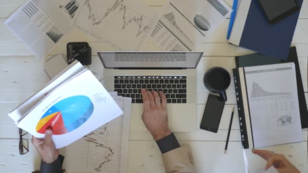 Top view male and female hands of young managers analyzing diagrams and graphs with statistics at wooden table in office. Arms of businessman typing text on laptop keyboard at white desk. Slow motion