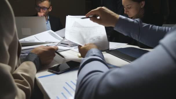 Tired business people sitting at table and discussing income charts and graphs at the end of working day. Colleagues analyzing financial reports in office. Business team examining documents at desk.