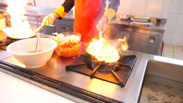 Profesionální kuchař s dvěma pánvičkami a kuchařským stylem v moderní restauraci. Samec vaří zeleninu v hořících pánvičích na sporáku. Koncept vaření. Dolly střela pomalý pohyb
