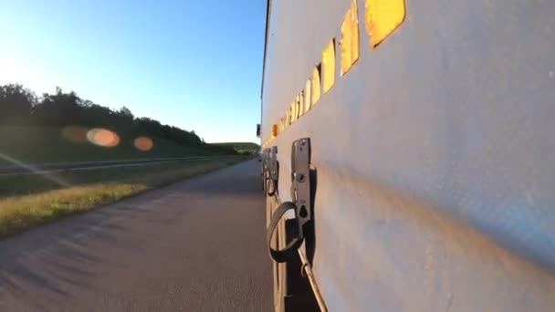 Truck driving on highway. Lorry rides through countryside. Point of view at the car traffic from the trailer of tractor going at asphalt road. Concept of trucking and commercial vehicle. Time Lapse