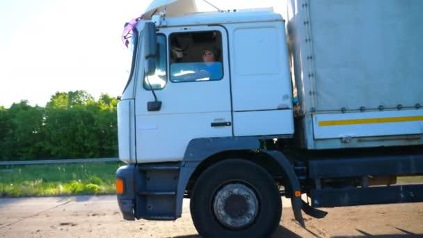 Náklaďák s nákladním přívěsem, který jede na dálnici a přepravuje zboží. Bílý náklaďák jezdí za slunečného dne do cíle přes venkovskou silnici. Jasné slunce svítilo na pozadí. Boční zobrazení pomalý pohyb
