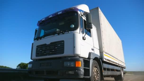 schlechte Sicht auf LKW mit Lastanhänger, der auf der Autobahn fährt und Güter transportiert. LKW fahren bei sonnigem Wetter durch die Landschaft. Transport- und Logistikkonzept. Zeitlupe aus nächster Nähe