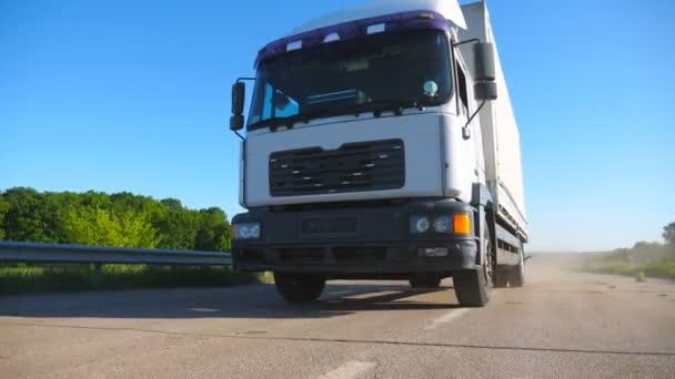 Vista bassa del camion con rimorchio merci che guida in autostrada e merci di trasporto. Camion in sella attraverso la campagna durante la giornata di sole. Bellissimo sfondo. Rallentatore Primo piano