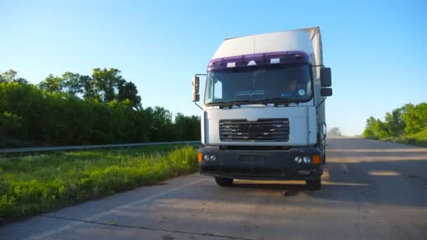 Frontansicht eines Lastwagens mit Ladeanhänger, der an sonnigen Tagen auf der Autobahn Güter transportiert. LKW fahren durch Landstraße. schöne Natur Hintergrund. Logistikkonzept. Zeitlupe aus nächster Nähe