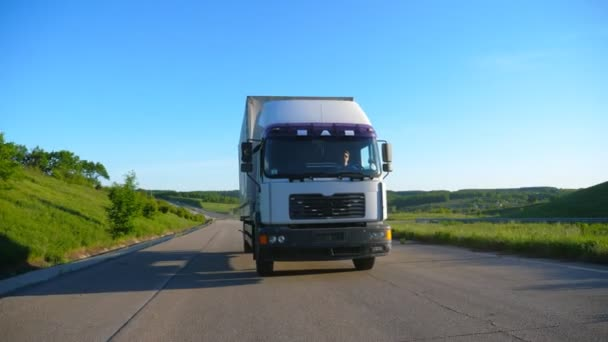 Front view of truck with cargo trailer speeding on highway and transporting goods at sunny day. White lorry riding through countryside road with beautiful nature landscape at background. Slow motion