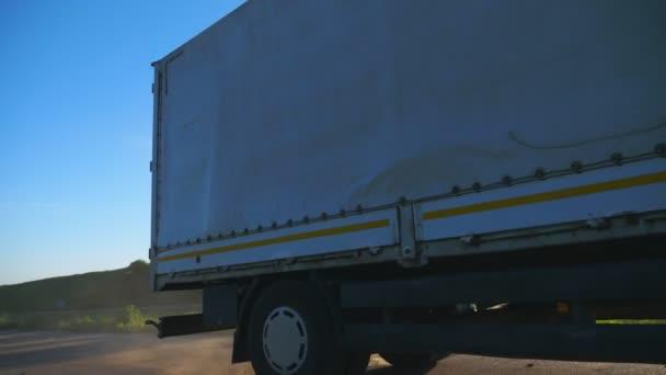 Náklaďák s nákladním přívěsem jezdíjel na silnici a přepravuje zboží v době západu slunce. Kamiona jezdila krajinou mezi krásným přírodním prostředím. Dopravní a logistická koncepce. Pomalý pohyb nízký pohled