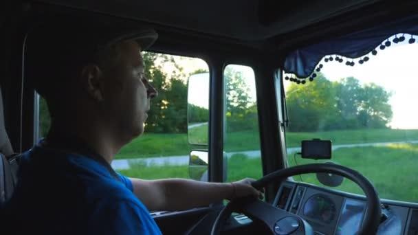Profilja az ember lovaglás a vidéken gyönyörű naplemente a háttérben. Tehergépkocsi-vezető ellenőrzése a teherautó vezetés a rendeltetési helyre. Közlekedési és logisztikai koncepció. A tehergépkocsi vezetőfülke belső megtekintése. Lassú Mo