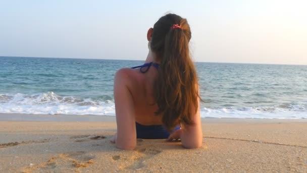 Fiatal lány a fürdőruhát feküdt a tenger parton és napozás. Gyönyörű kaukázusi nő pihentető óceán partján a nyári szünetben utazik. A pihenés fogalma az üdülőhely partvidékén. Lassú mozgás közelről