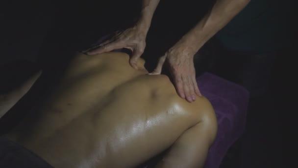 Svalnatý sportovec ležící na masážním stole a profesionální masér, který mu masíruje záda olejem v tmavé místnosti. Mužské ruce masagistky, které masírují mladého sportovce v salónku. Horní pohled