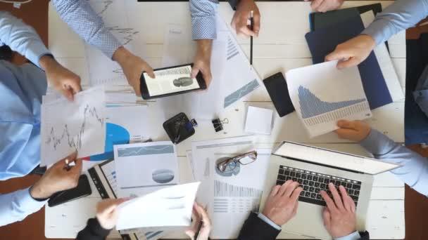 Männer- und Frauenhände von Geschäftsleuten planen Strategie für Unternehmensprojekte im Büro. Business-Team am Tisch sitzen und die Finanzkurven prüfen. Mitarbeiter prüfen Dokumente am Schreibtisch